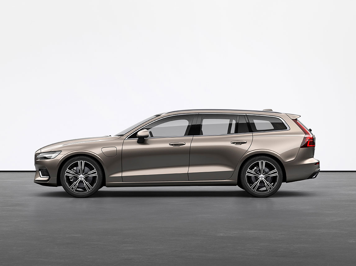 A luminous sand metallic Volvo Wagon V60 Recharge plugin hybrid standing still on grey floor in a studio