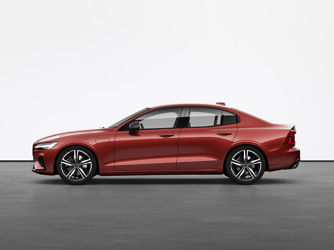 A red Volvo Sedan S60 Recharge plugin hybrid standing on grey floor in studio