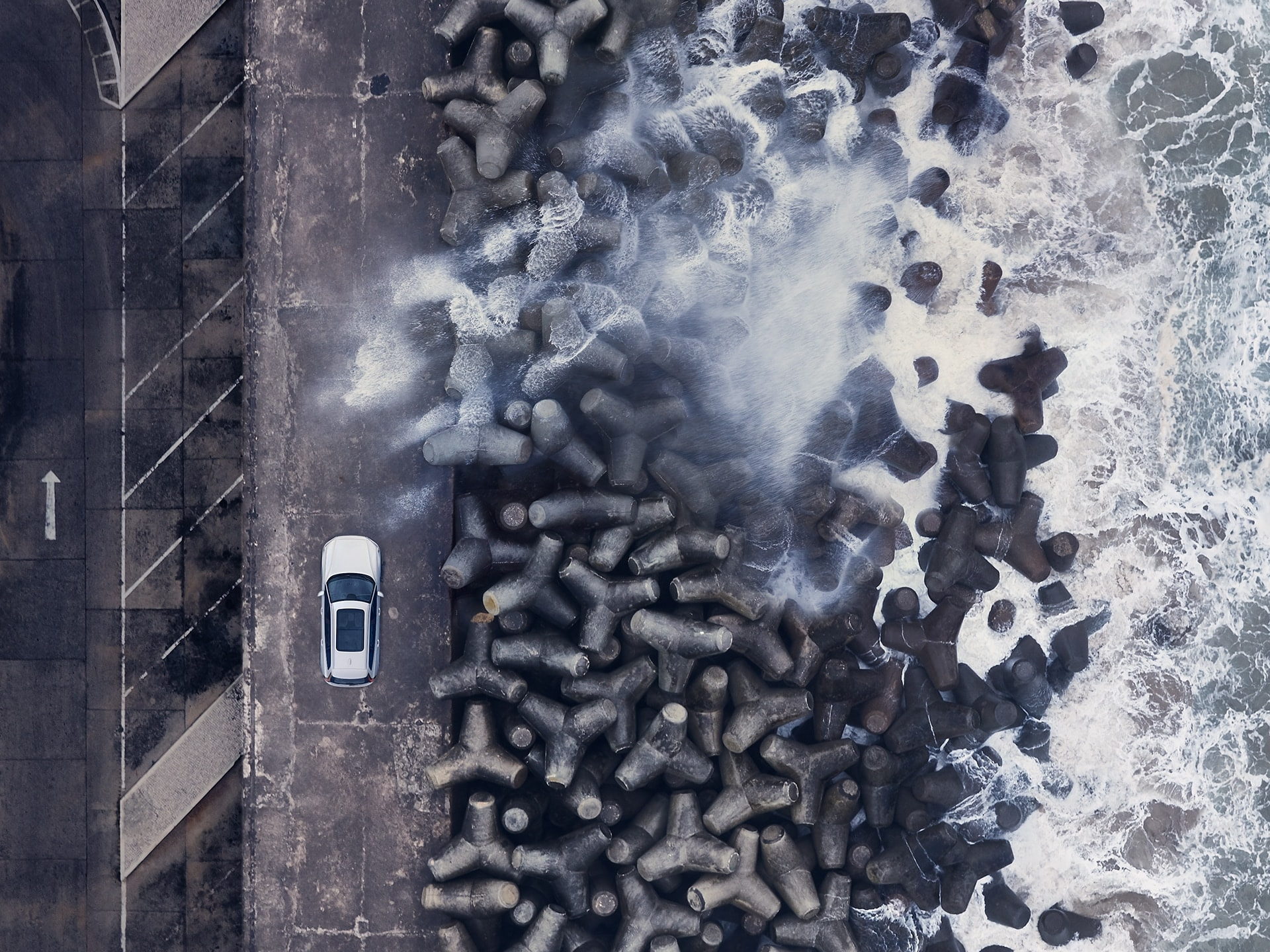 A Volvo V60 Cross Country is parked on a pier with breakwater