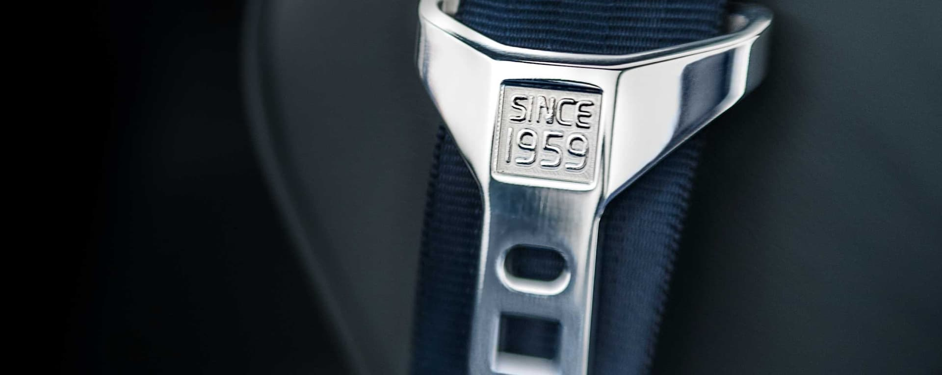 """A safety belt in grey with the text """"Since 1959"""" engraved on the buckle."""