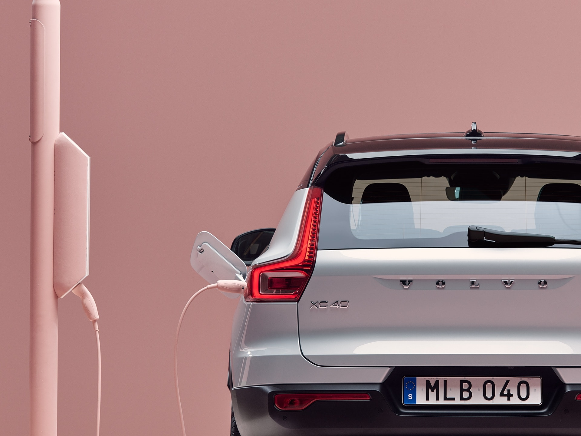 View from the rear of a Volvo XC40 Recharge Pure Electric SUV plugged in to a charging box installed on a light post.