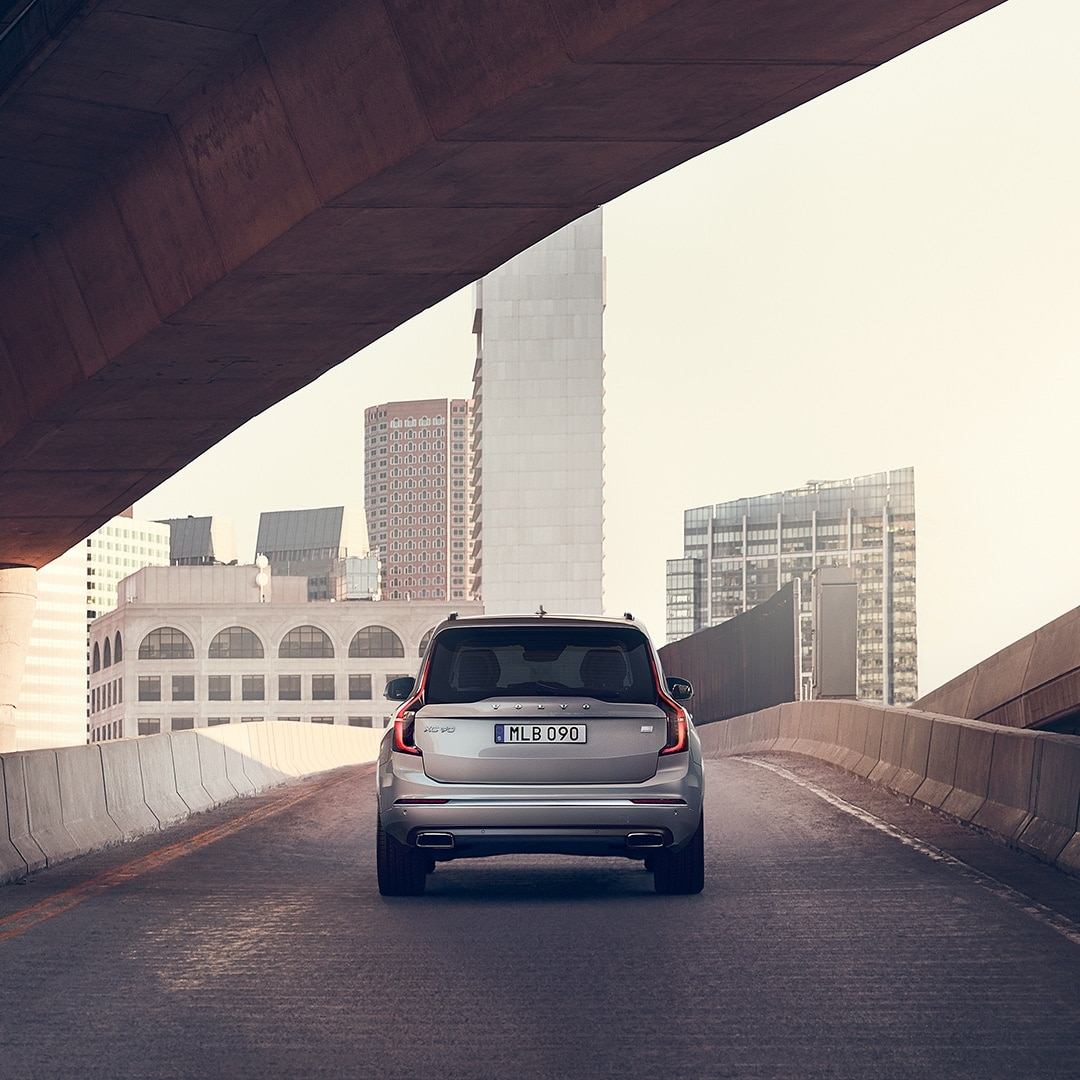 A Volvo XC90 Recharge drives on a bridge
