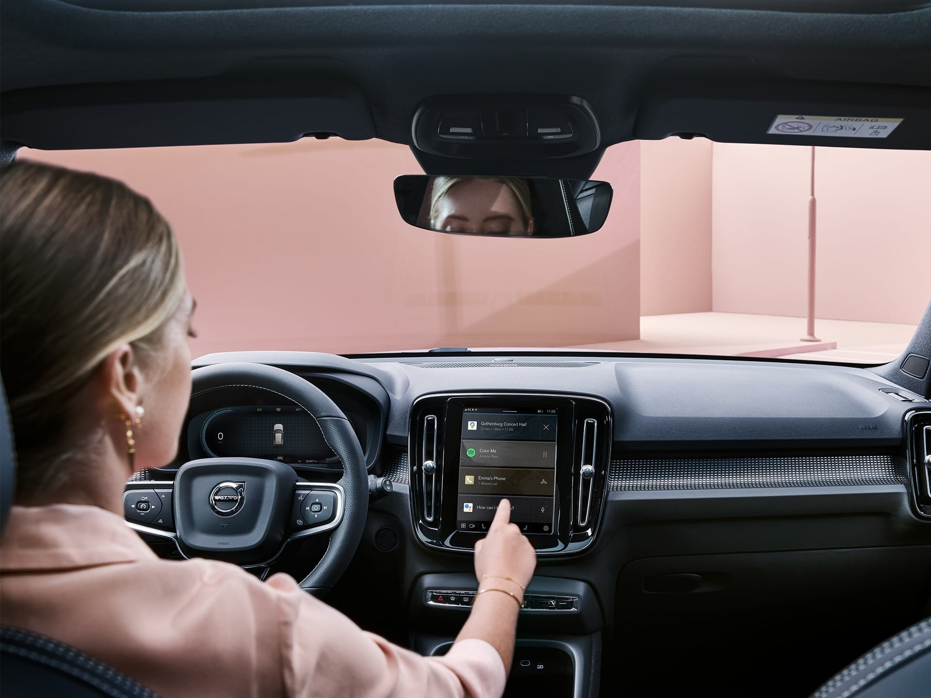 A woman inside a Volvo XC40 Recharge car, using the connectivity system