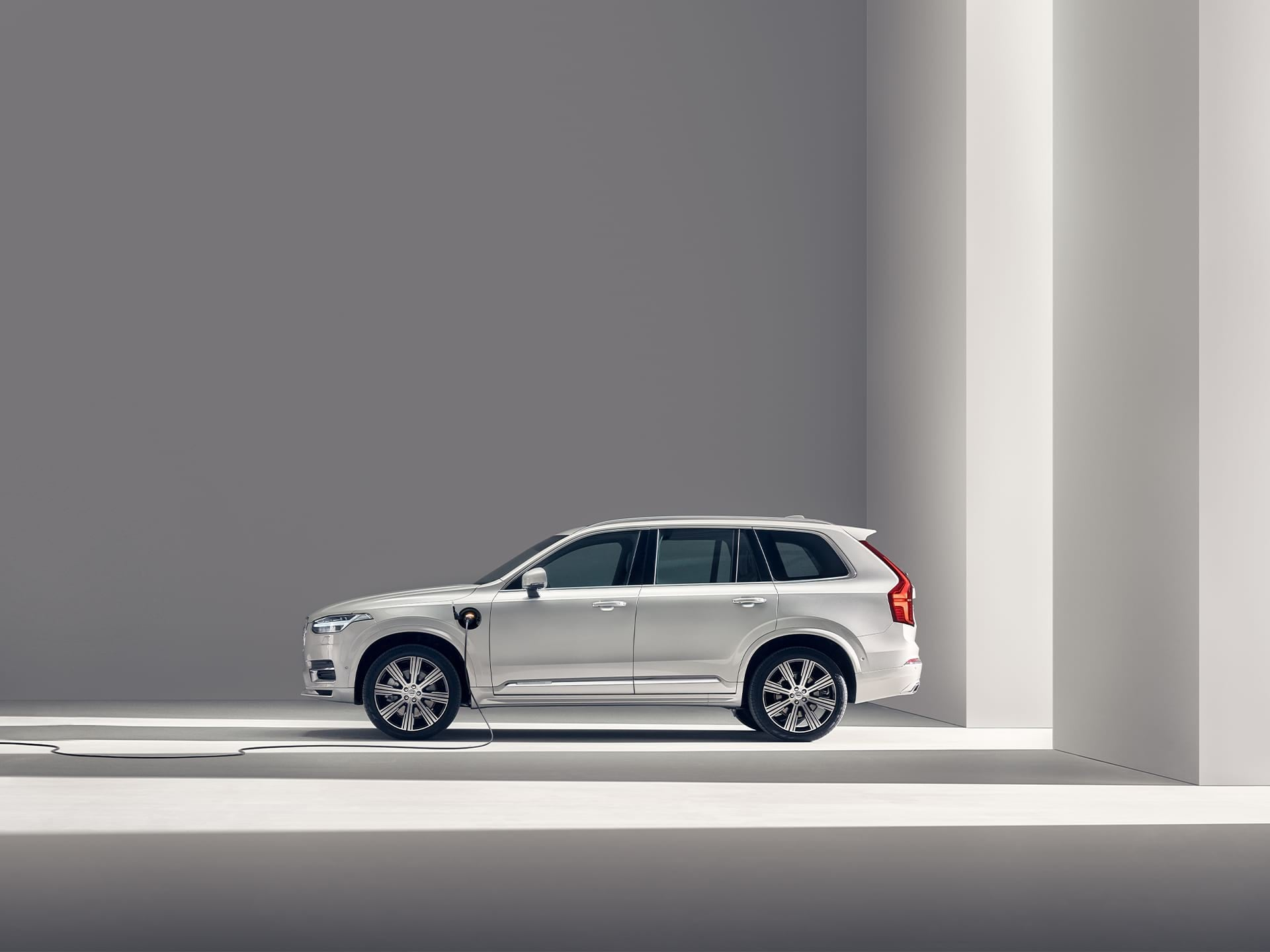 A grey Volvo XC40 full electric SUV being charged in a pink background