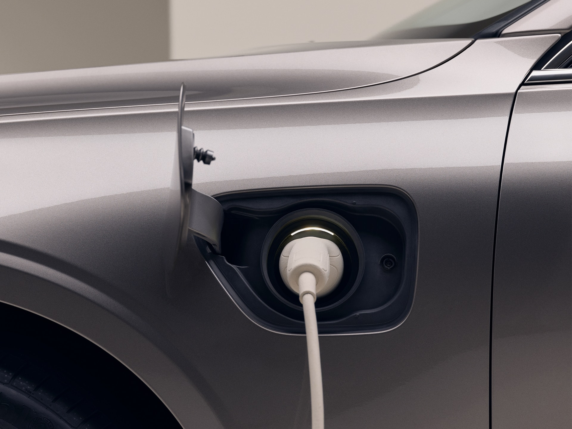 Close-up of front left of a grey Volvo with a white charging cable inserted in the car's charging port