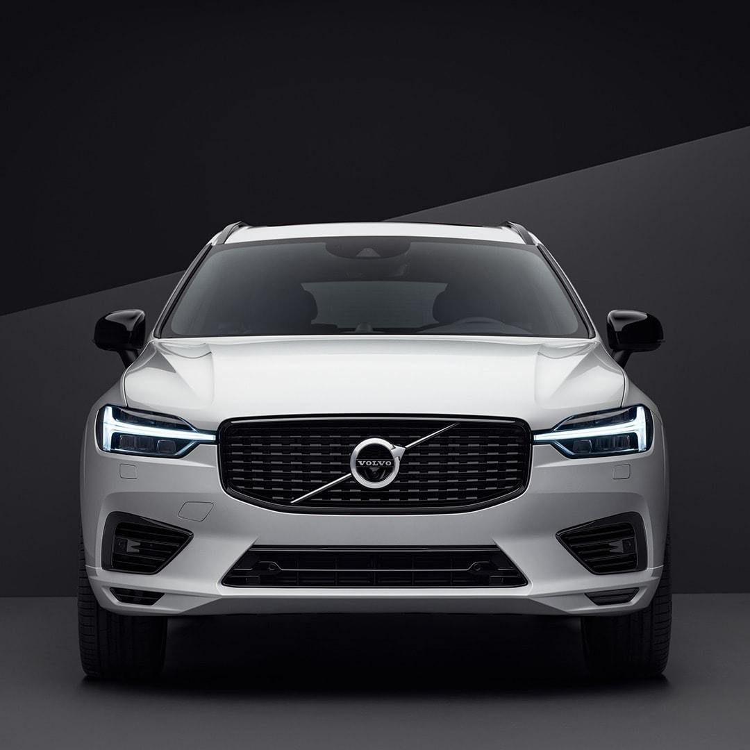 Valkoisen Volvo XC60:n ulkopuoli edestä, pysäköity mustaan ympäristöön