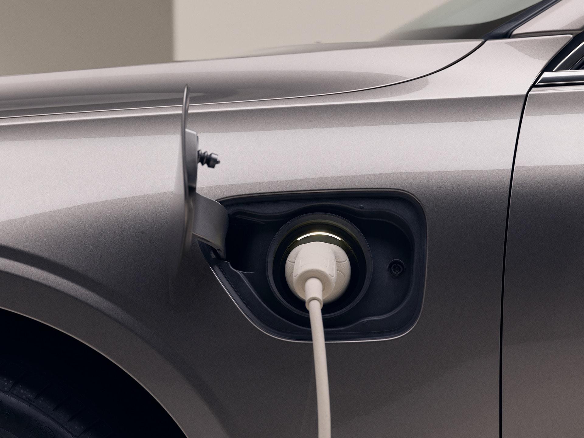 Lähikuva harmaan Volvon vasemmasta etukulmasta valkoinen latauskaapeli kytkettynä auton latausliitäntään