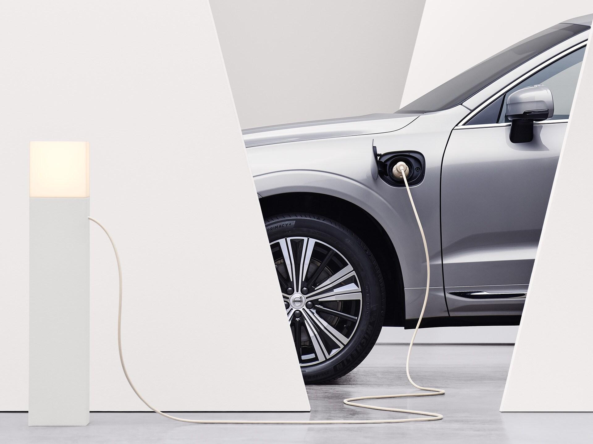 SUV Volvo argent lumineux en stationnement, branché sur une borne de recharge