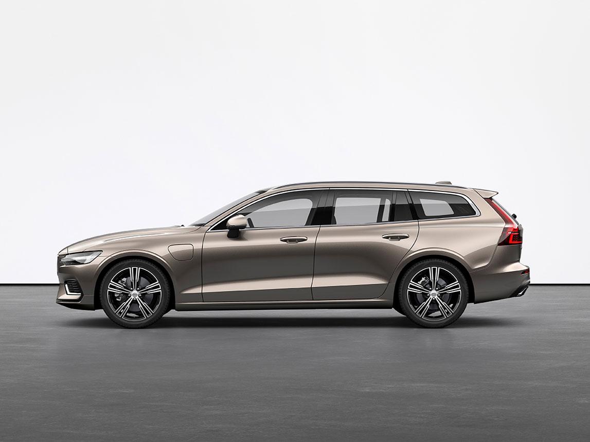 A luminous sand metallic Volvo Estate V60 Recharge plugin hybrid standing still on grey floor in a studio