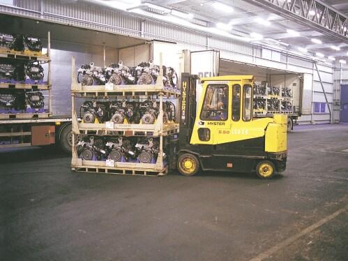 Chariot élévateur jaune déplaçant des palettes de pièces détachées de voitures.