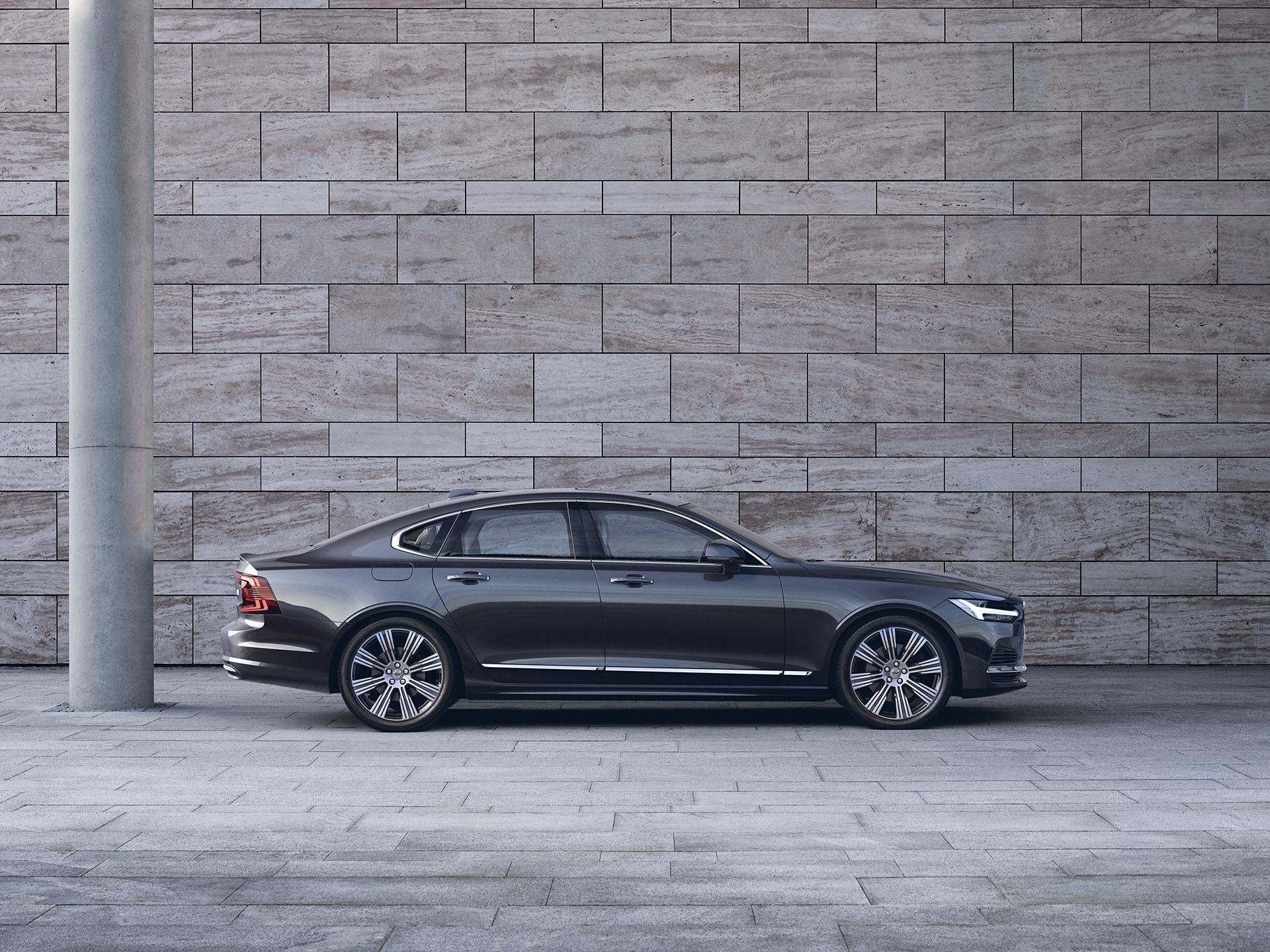Une Volvo S90 sombre est parquée devant un mur gris