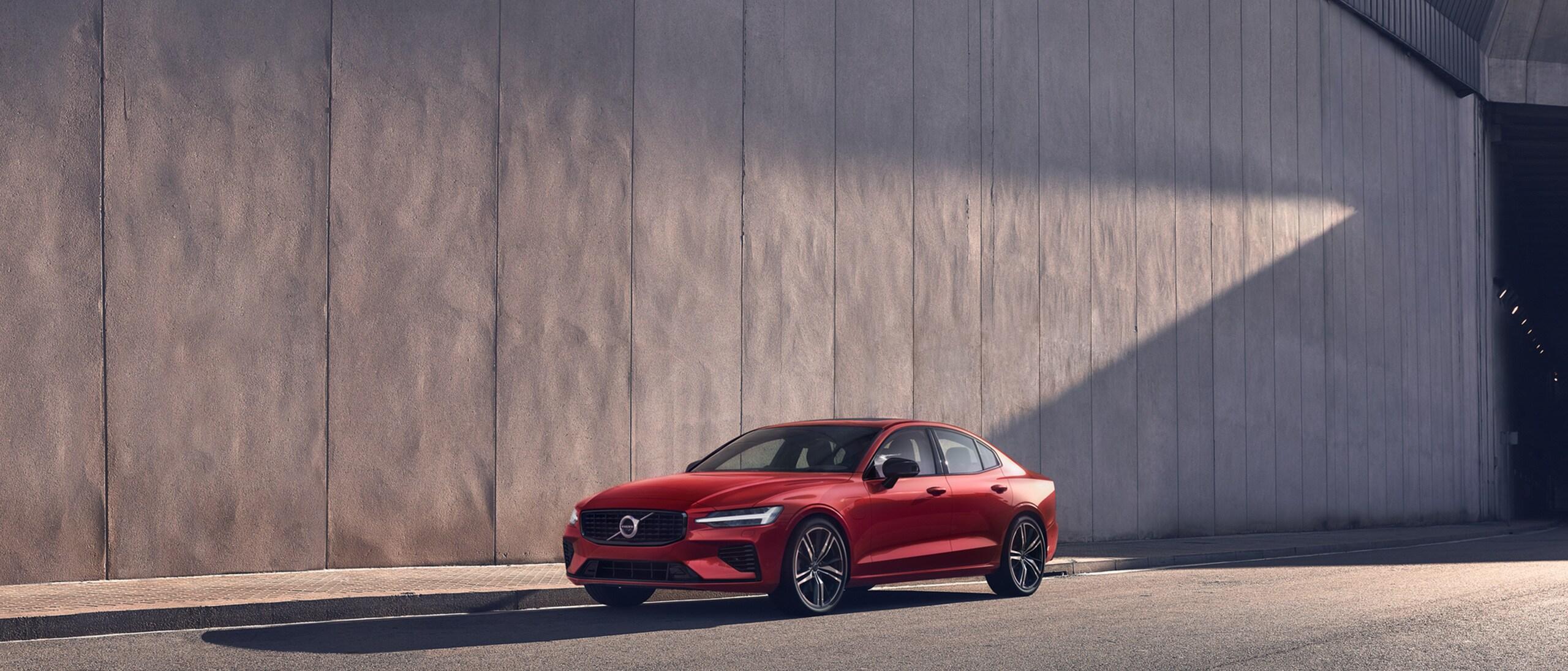 Une Volvo S60 Recharge rouge stationnée devant un mur beige