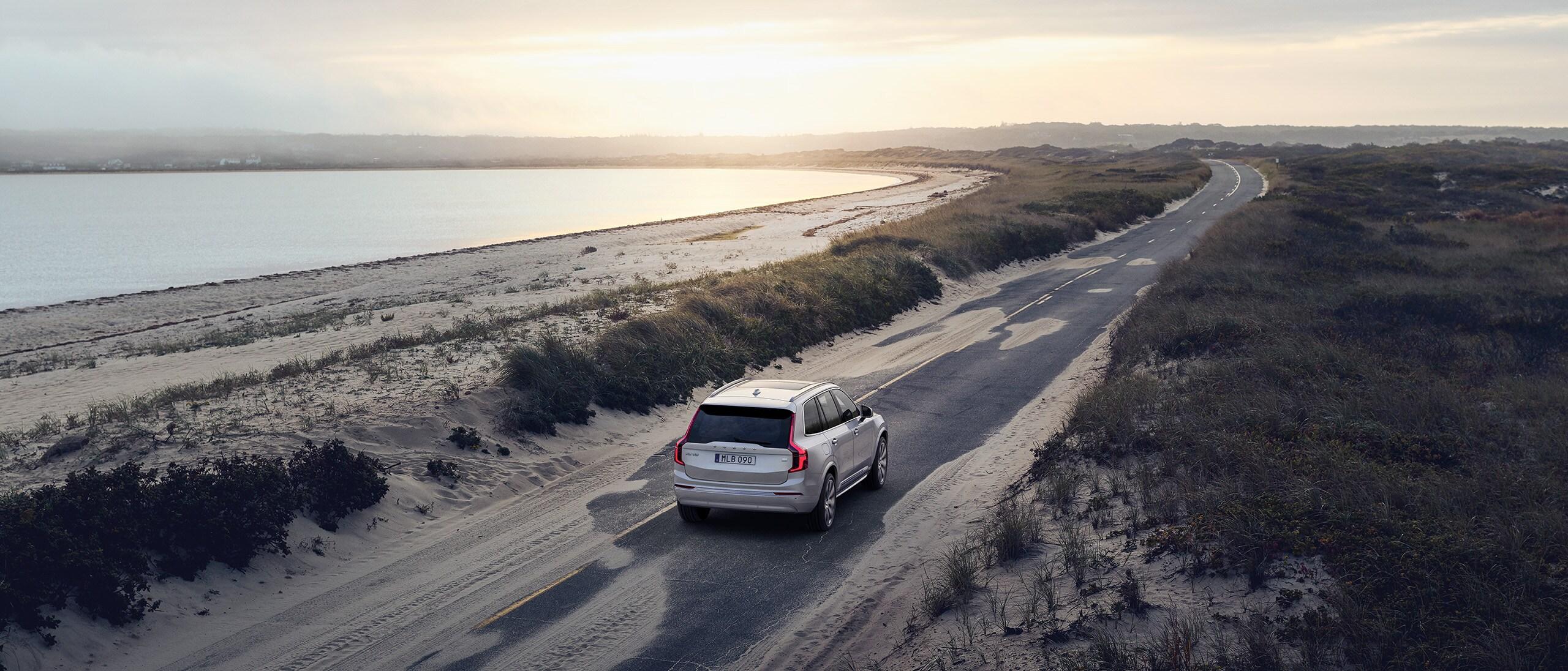 SUV Volvo XC60 gris roulant à l'aube sur une route de campagne entourée de champs