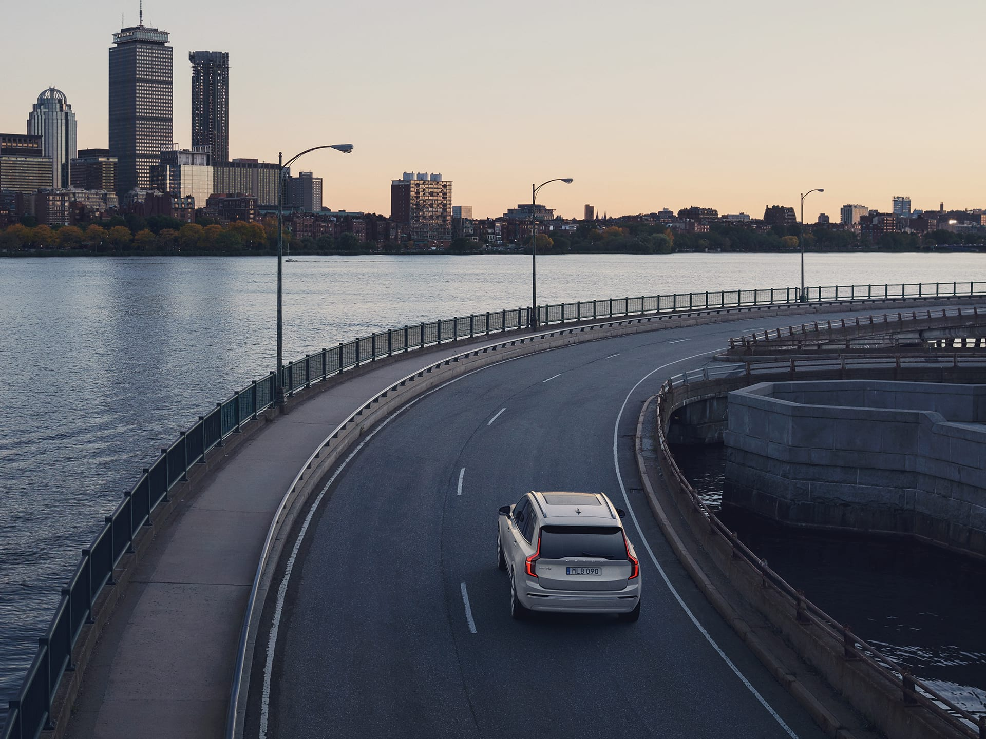 Grand SUV 7places Volvo XC90 suivant une courbe le long d'une rivière.