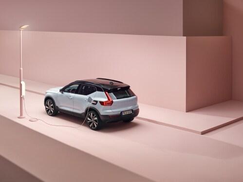 Το αμιγώς ηλεκτρικό SUV Volvo XC40 Recharge συνδεδεμένο σε έναν σταθμό φόρτισης που είναι εγκατεστημένος σε μια κολόνα φωτισμού.