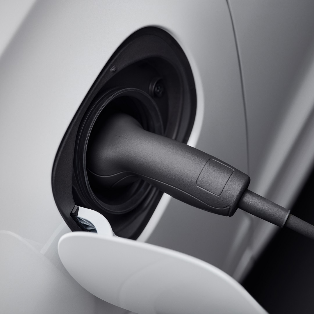A white Volvo car's charging cap being opened and charger plugged in.