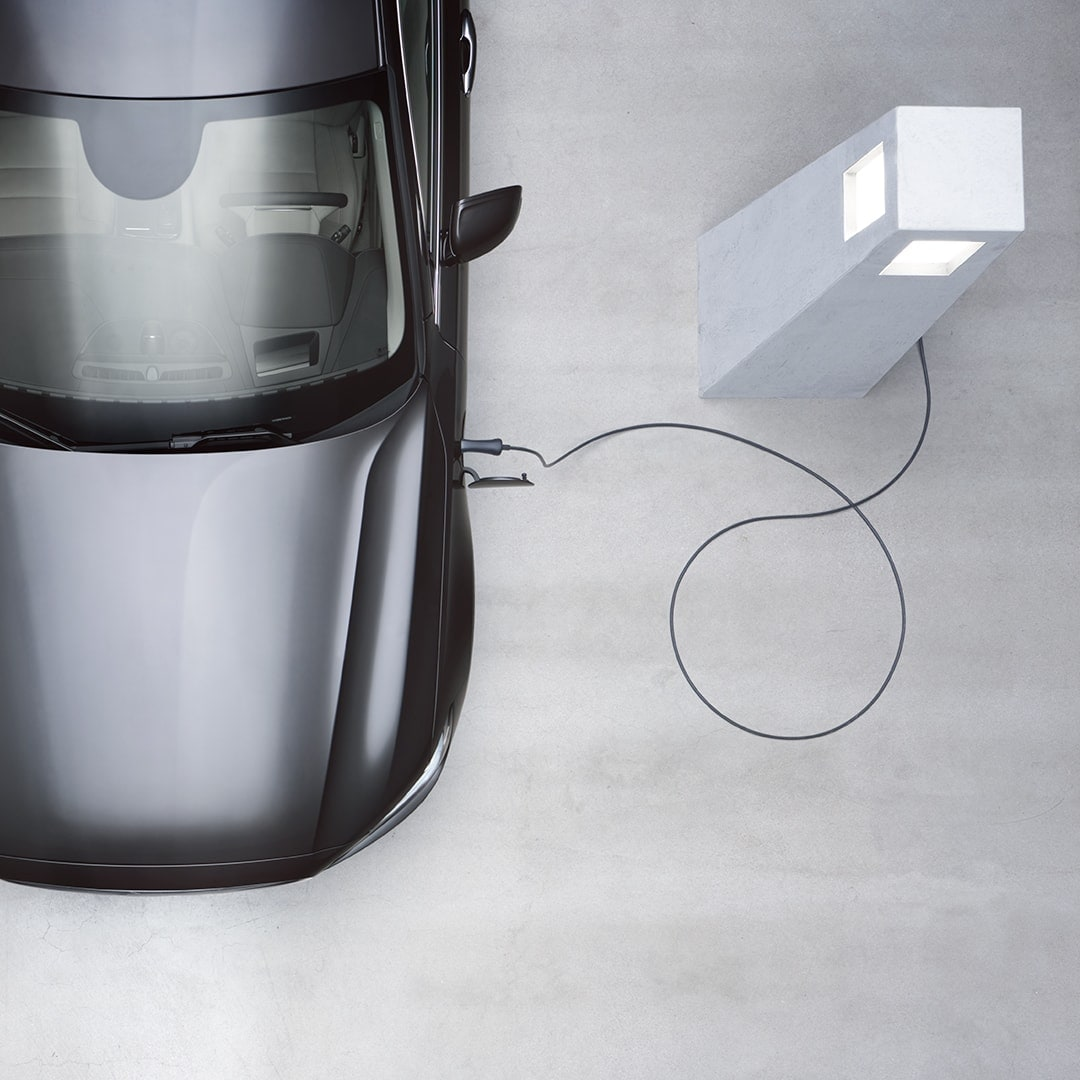A grey Volvo car from above, being charged via a charging station