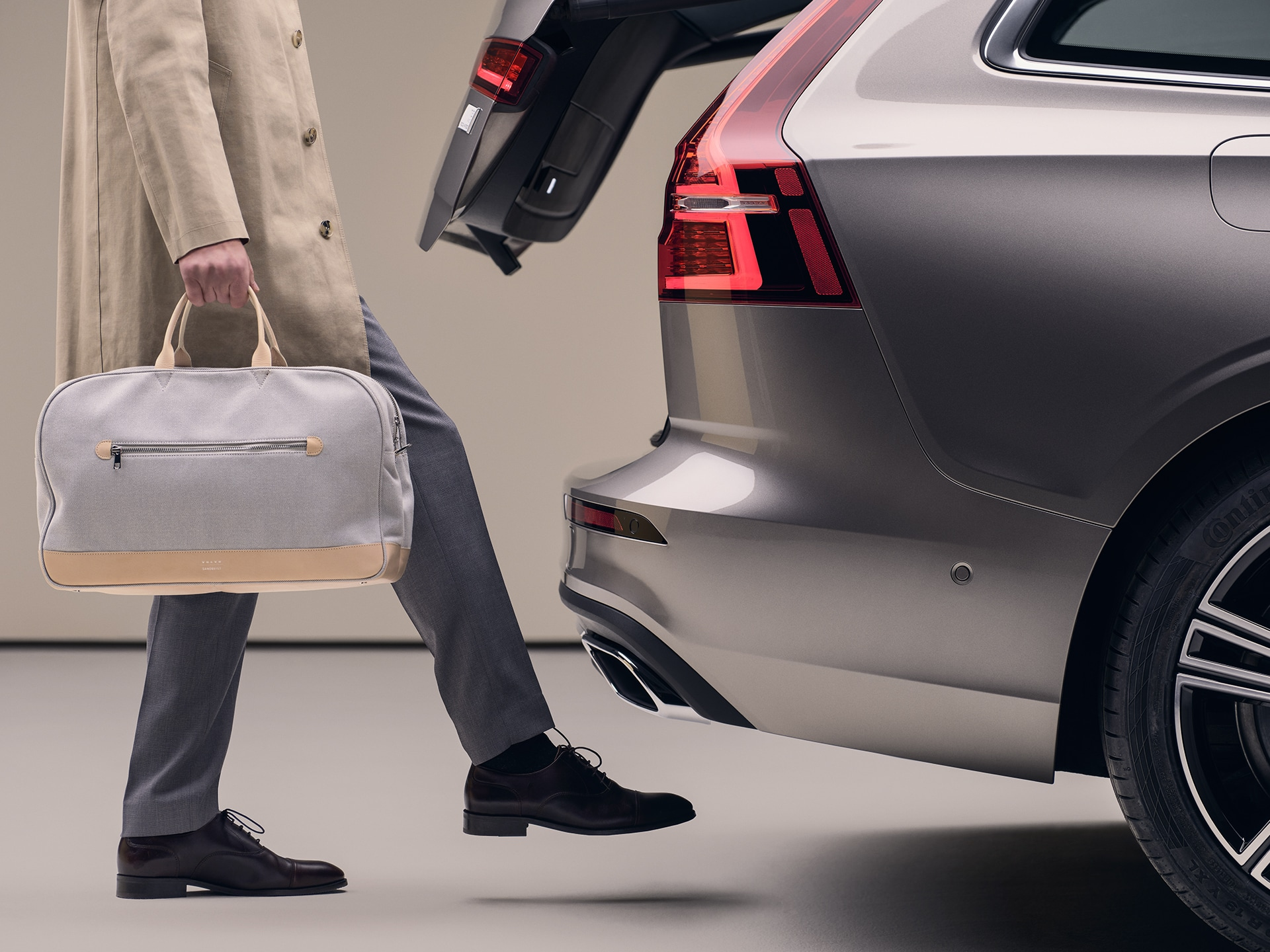 A man with a sports bag in his hand, moving his foot under the rear bumper to open the tailgate