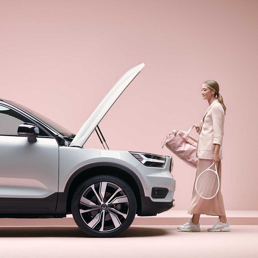 Djevojka plave kose sa sportskom torbom i teniskim reketom u ruci ide prema svom automobilu XC40 Recharge.