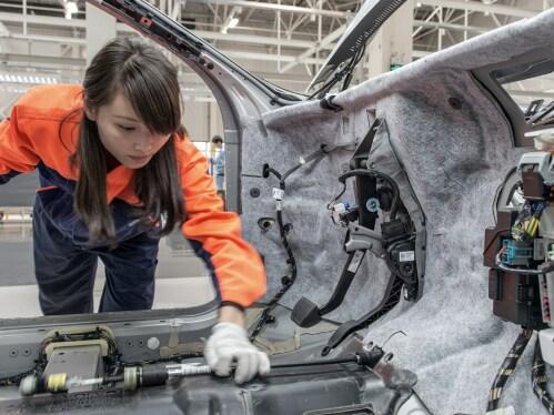 Egy nő a gyárban az autó karosszériáját vizsgálja.