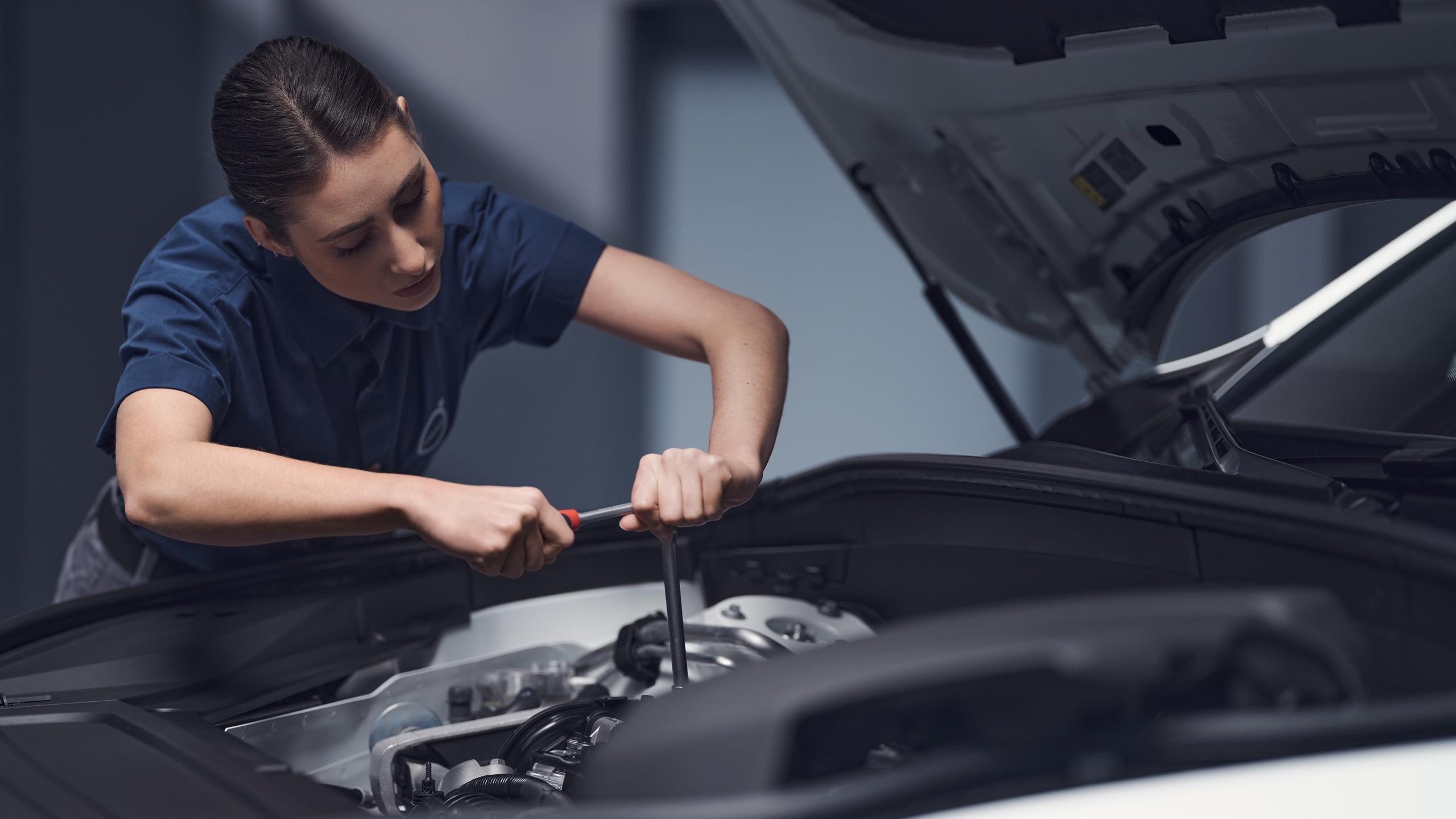 Közelkép egy női Volvo technikusról, amint egy motoron dolgozik.