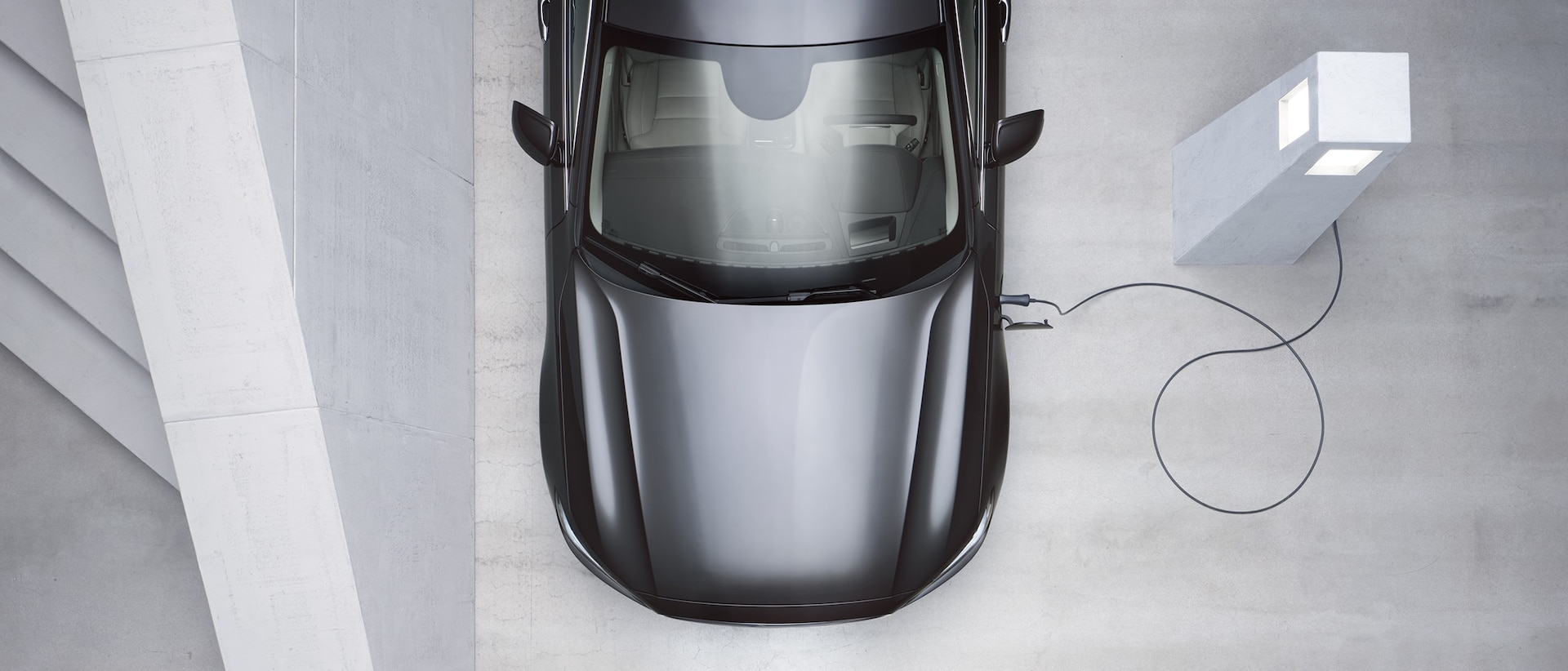 Egy szürke Volvo felülnézetből, a töltőállomáson töltés közben