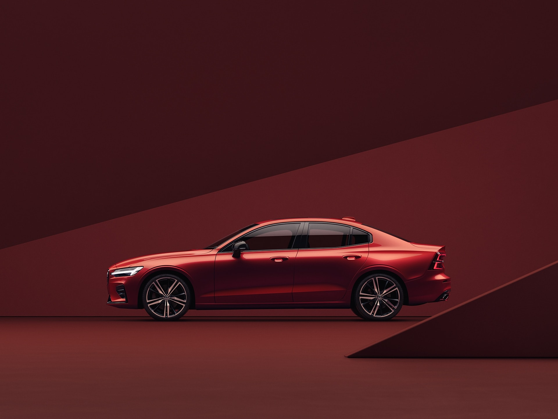Piros Volvo S60 piros környezetben parkol.