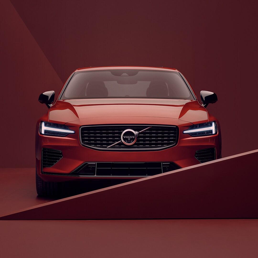 Egy piros Volvo S60 Recharge elejének a külső megjelenése piros környezetben.