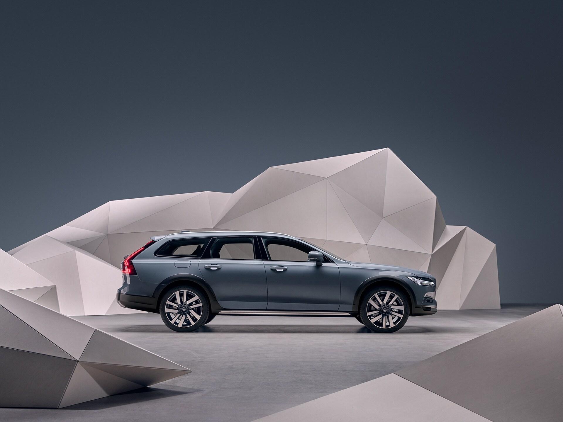Kagylókék metál Volvo V90 Cross Country, amely egy művészien festett fal előtt parkol.