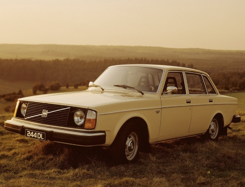 A Volvo 240 standing on a hill.