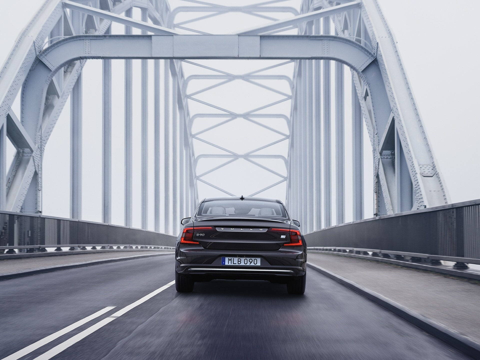A Volvo S90 Recharge is driving on a bridge on a cloudy day.
