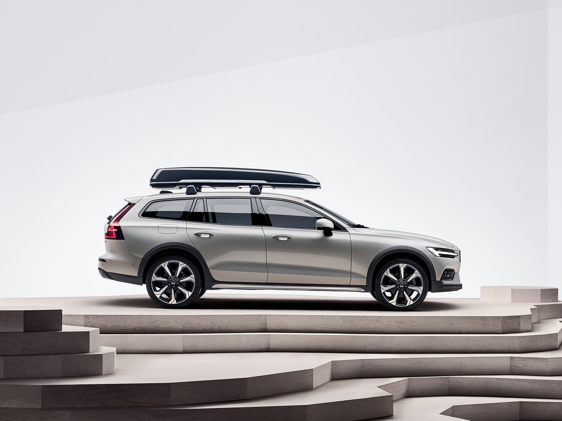 A beige Volvo V60 Cross Country with a roof box is parked on top of a staircase.