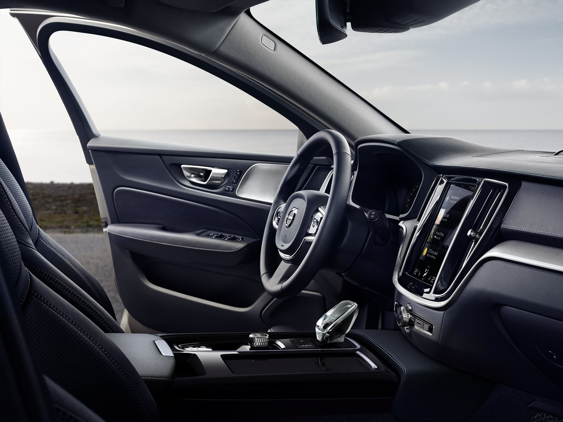 Front interior of a V60, the driver door is open.