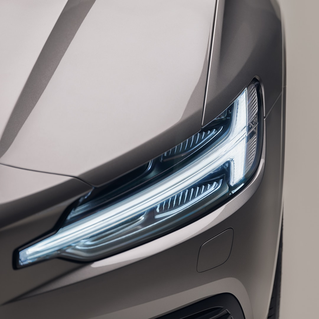 A closeup of the front headlights of a beige Volvo V60 Recharge.