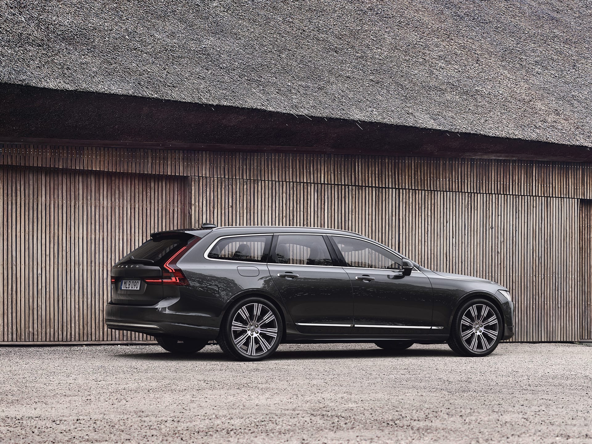 A Volvo V90, parked outside against a wooden wall.