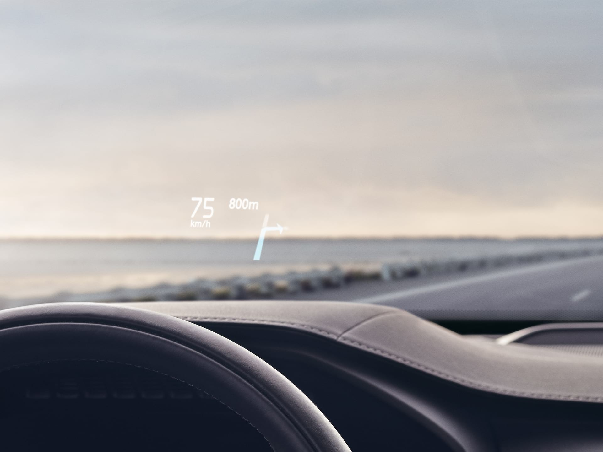 Inside a Volvo, head-up display showing driving speed and navigation on the windshield.