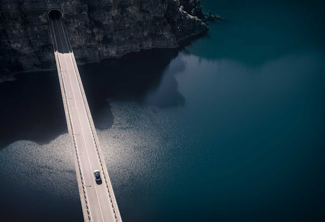 A Volvo car passing a bridge over water.