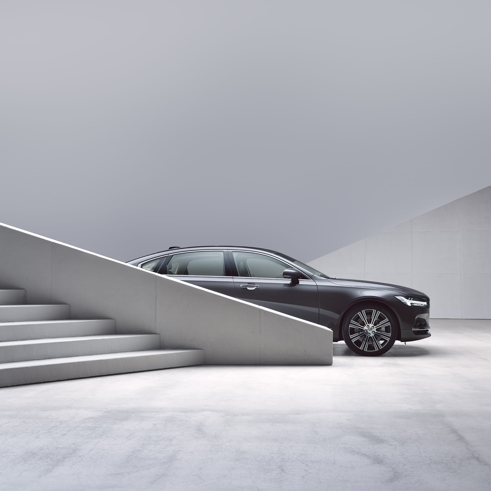 A Volvo S90 partially obscured by stairs
