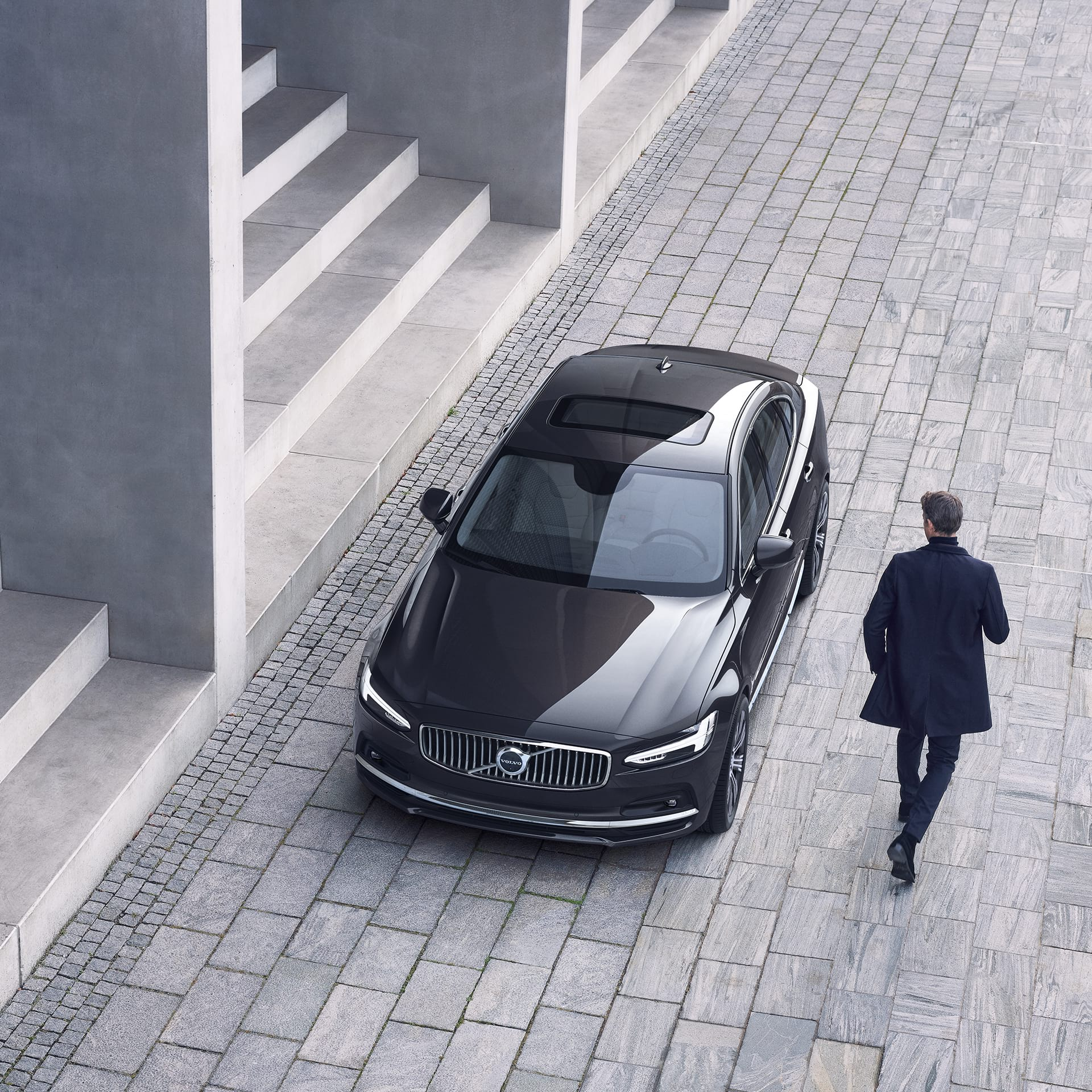 A Volvo S90 is parked in front of a set of stairs, a man walks towards the car