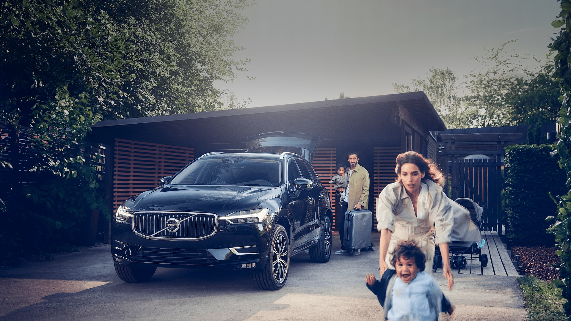 A black Volvo XC60 SUV and a family with young children trying to pack up and leave home.