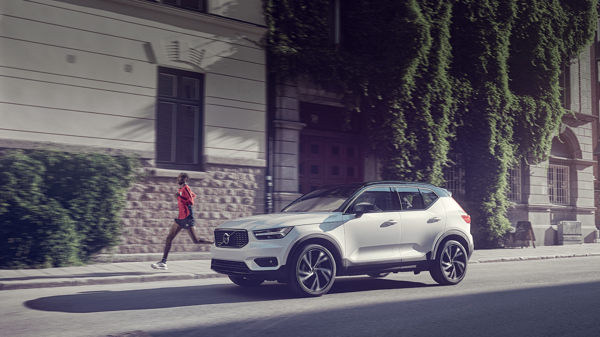 A white Volvo XC40 SUV is passing a jogger in a downtown street.