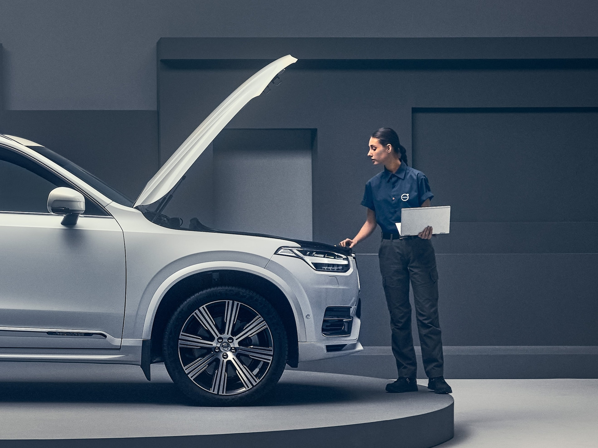 White Volvo with raised bonnet being worked on by female technician.