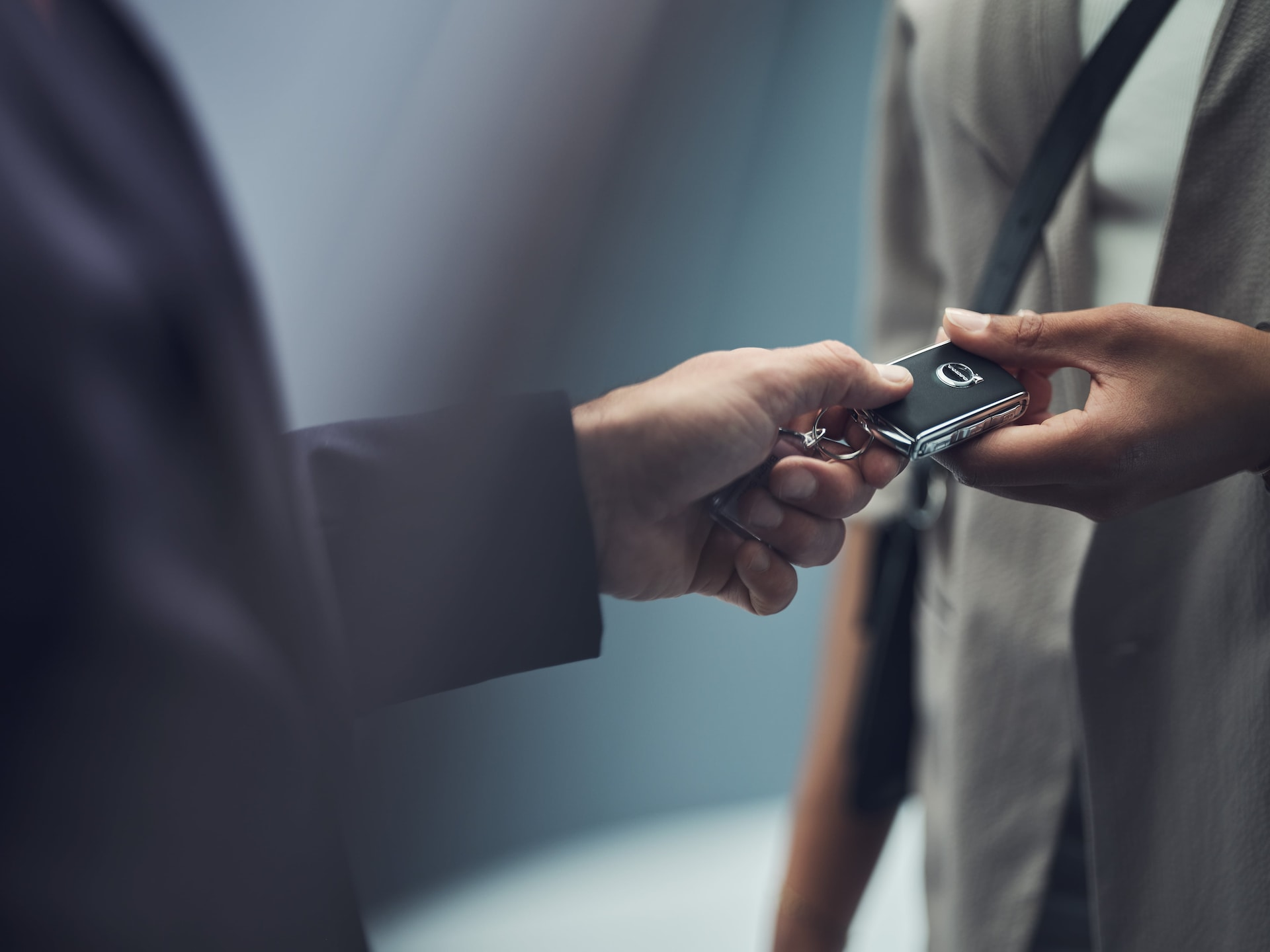 One person handing over a Volvo key to another person.