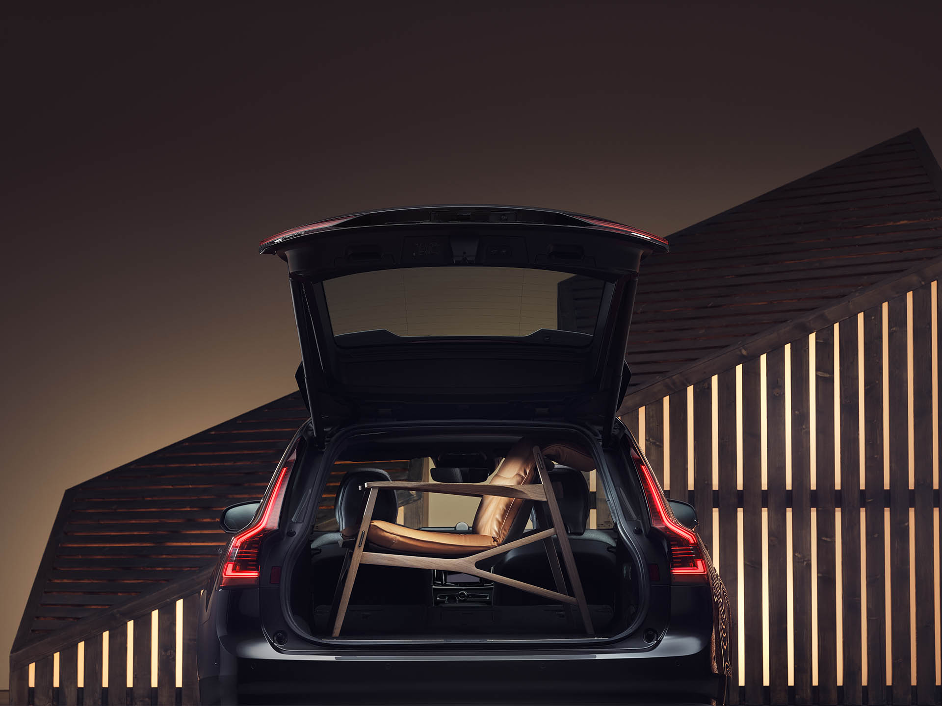 The boot space of a Volvo Estate is filled up by a brown elegant armchair