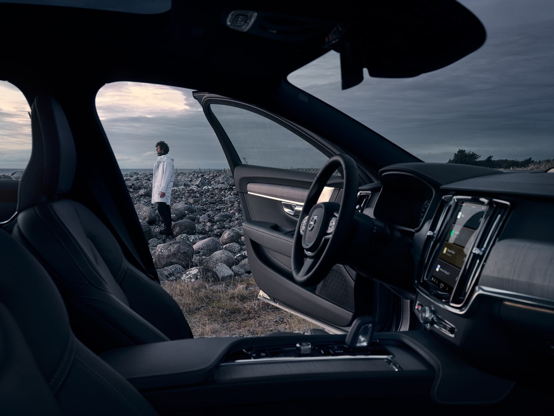 Inside a V90 Cross Country with black interior, a man is standing outside.