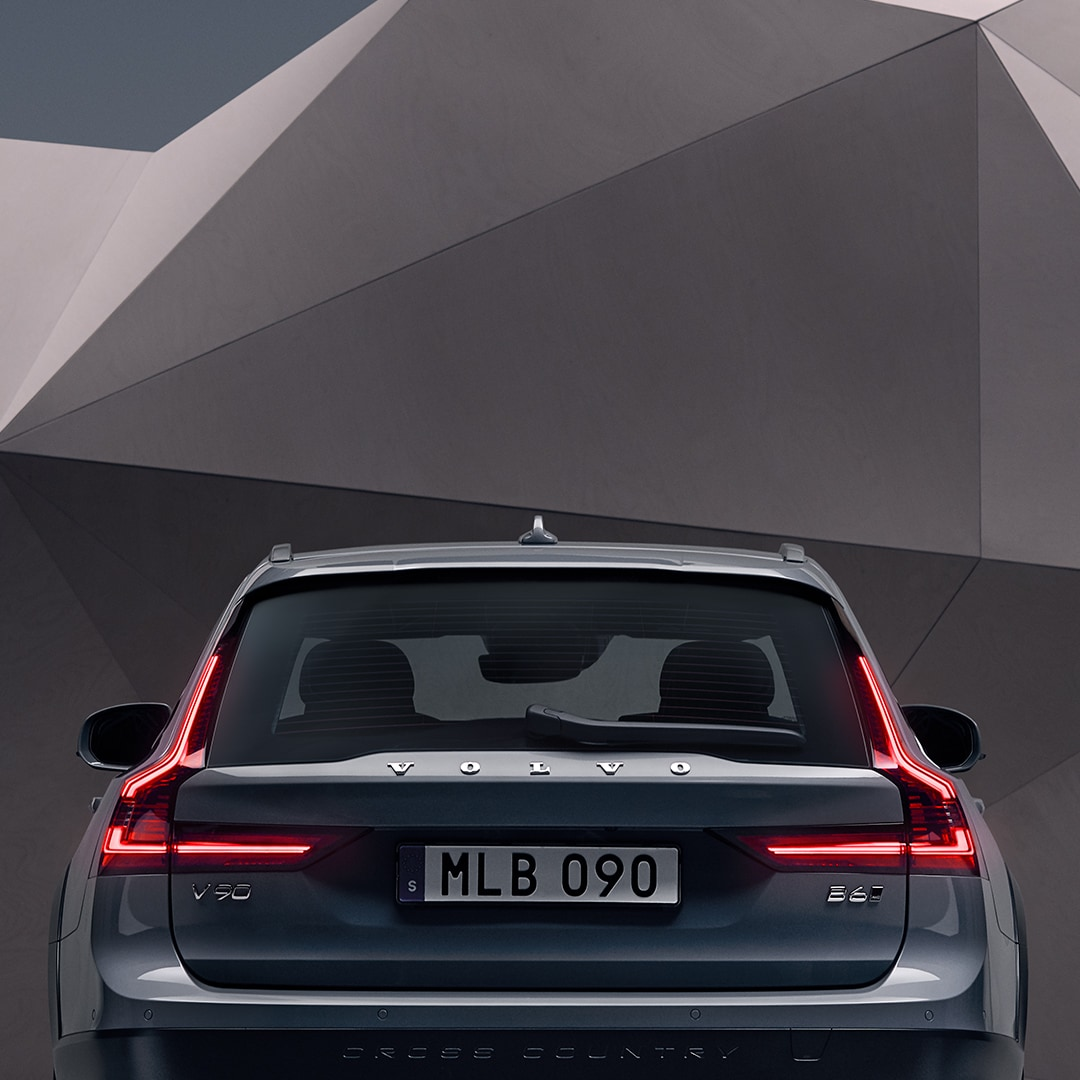 The rear exterior of a mussel blue metallic V90 Cross Country standing in front of an artistic wall.