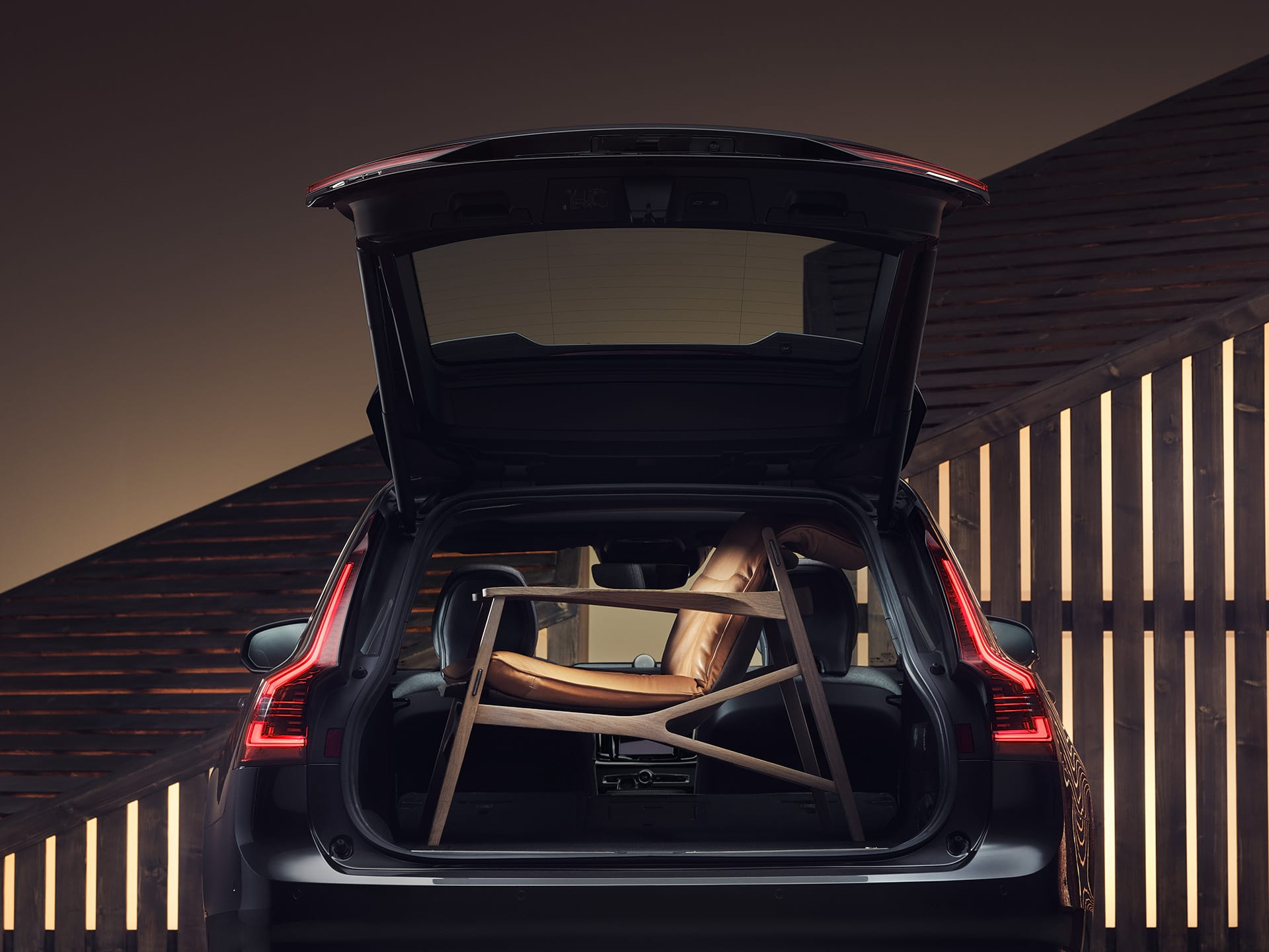 The boot space of a Volvo V90 Recharge holding an elegant, brown armchair.