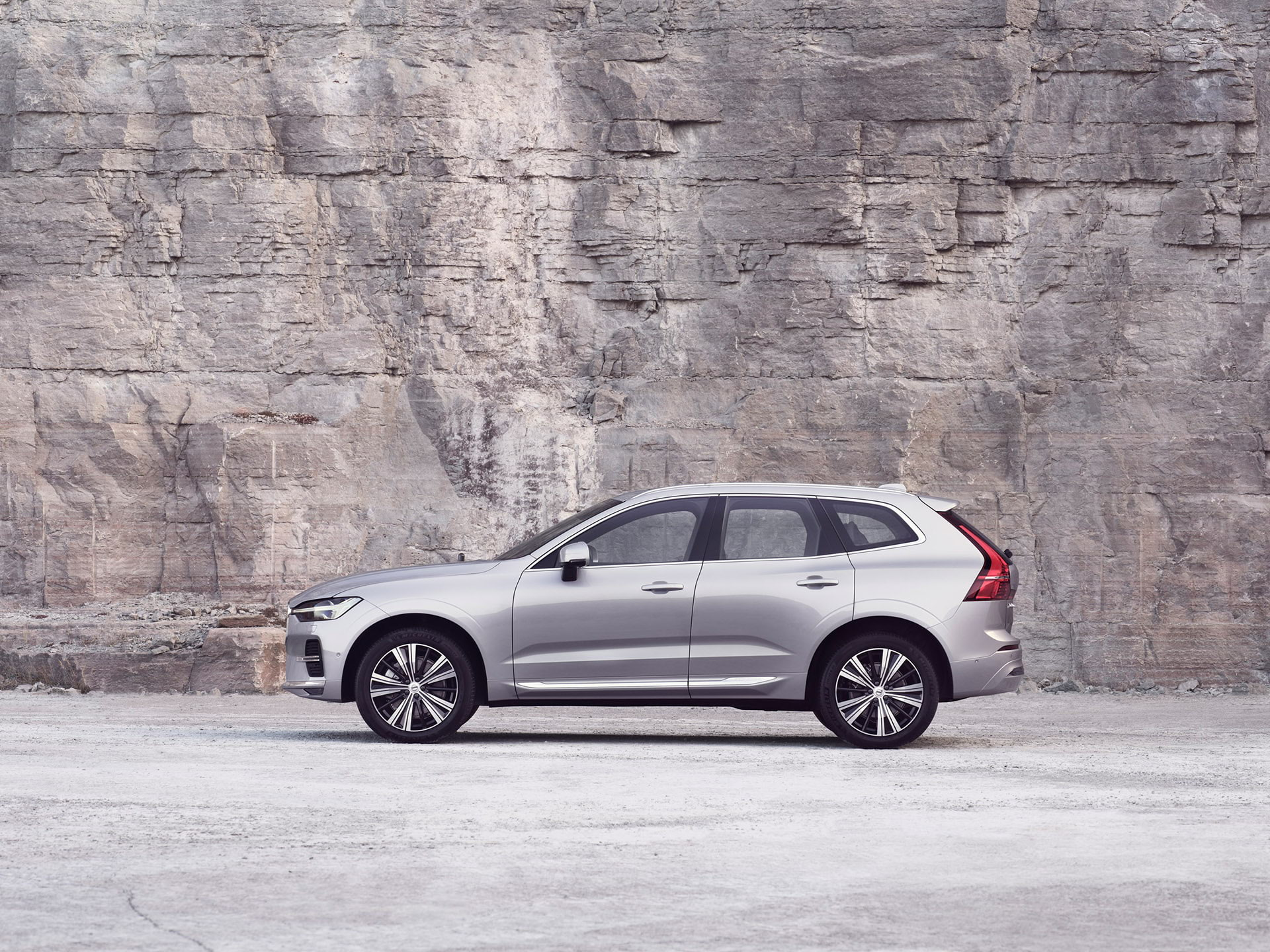 A silver Volvo XC60, charging in white surroundings.