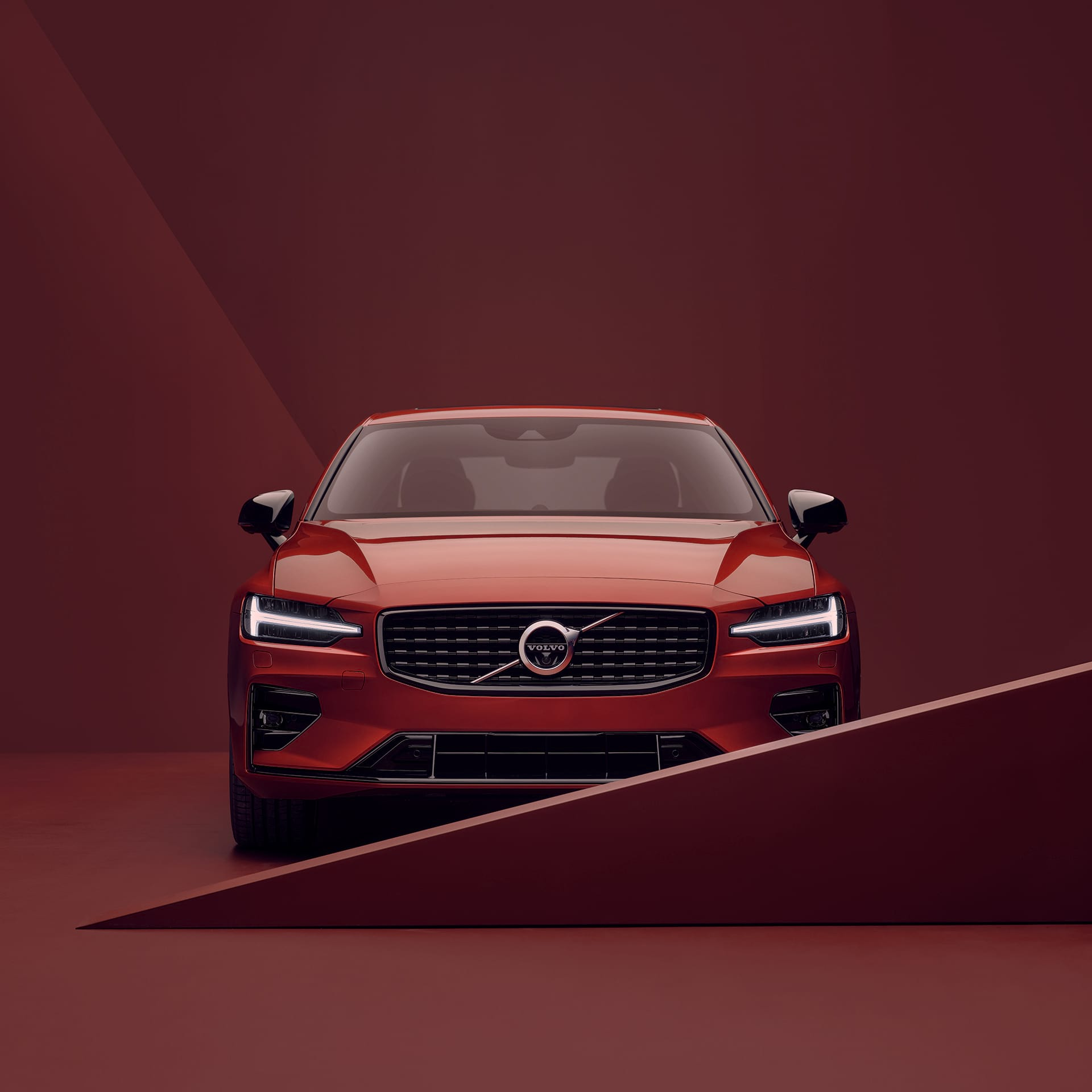 The front exterior of a red Volvo S60 in a red surrounding