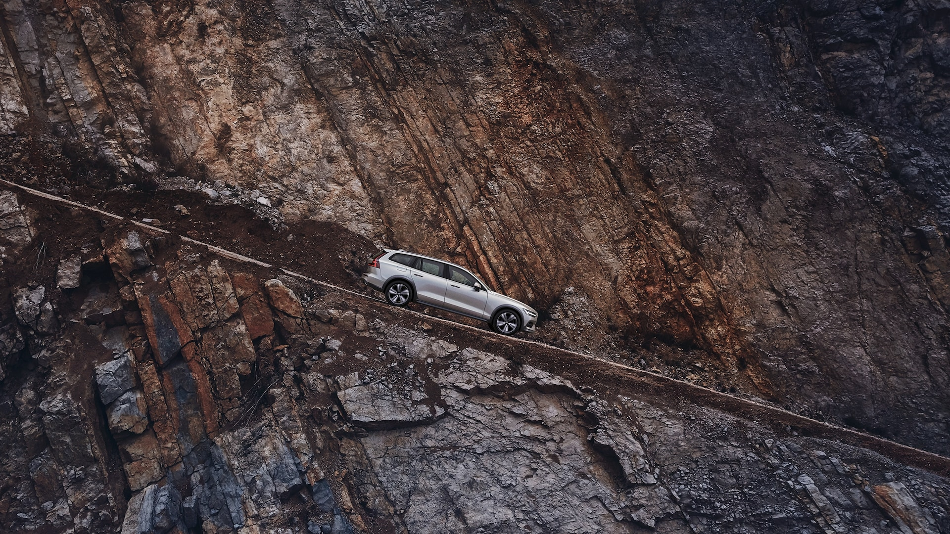 A Volvo V60 Cross Country drives down a mountainous road